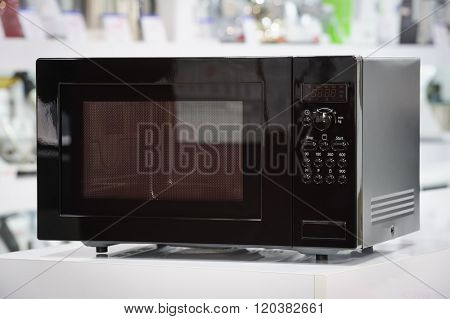 single black microwave oven at retail store shelf, defocused background