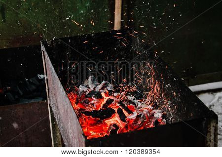 The glowing embers ascending over a large bonfire in brazier