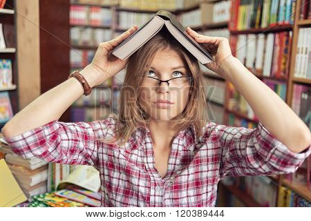 Cute female student in the library getting knowledge from book