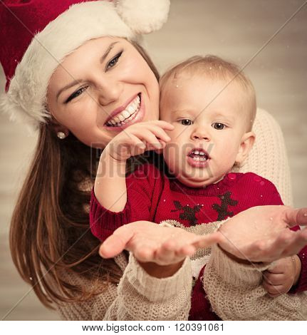Family celebrating Christmas. Happy mother and her little cute child looking at snowflakes in cold winter days. Young attractive woman holding her beautiful baby wearing warm clothes and Santa hat.
