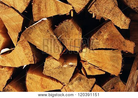The Stack Of The Snowy Firewood On Old Wooden Background