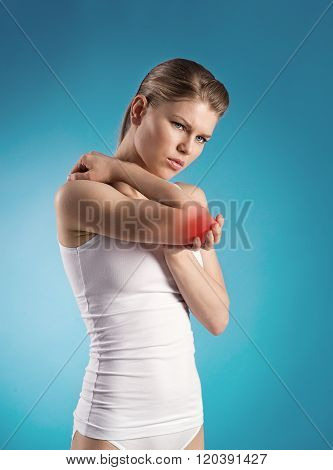 Portrait of female suffering from arthritis and massaging her painful elbow. Tendon inflammation.