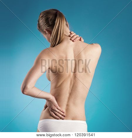 Spine therapy. Close-up of woman with naked back suffering from backache over blue background.