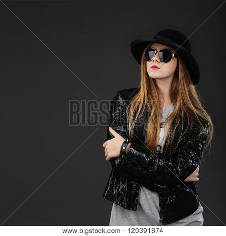 Portrait Of Beautiful Young Girl Wearing Black Felt Hat, Sunglasses And Leather Jacket