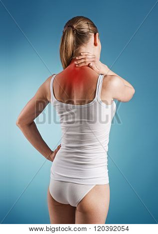Woman suffer from neck pain, over blue background. Portrait of young girl touching her sick nape.
