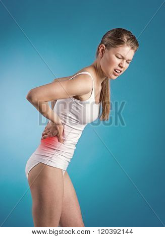 Stressed young woman with back pain touching her painful loin.