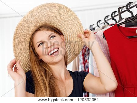 Portrait of spree shopping woman trying summer hat waiting for vacation. Young beautiful Caucasian woman model choosing accessories in retail shop.