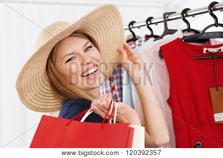 Close-up of beautiful blond lady choosing summer hat standing at clothes rack in shopping mall. Young happy smiling Caucasian woman buying accessories in small boutique.