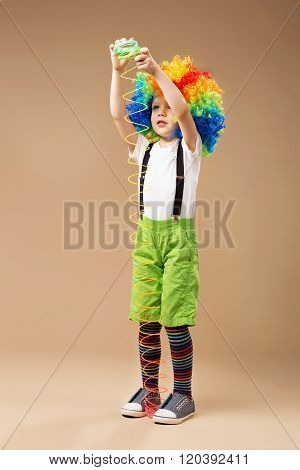 Little boy in clown wig smilling and playing with Magic Spring. Full-length portrait of Happy clown boy with large colorful wig. Little clown boy with colorful hair and spring toy.