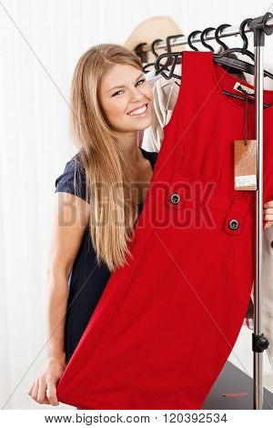 Smiling female shopper trying new dress in shopping boutique. Portrait of lovely Caucasian woman model holding elegant clothes in retail store.