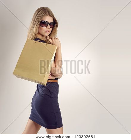 Glamour blonde lady in glasses with a shopping bag.