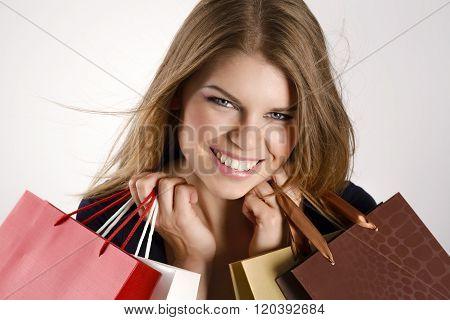 Portrait of glamorous spree female shopper holding bags