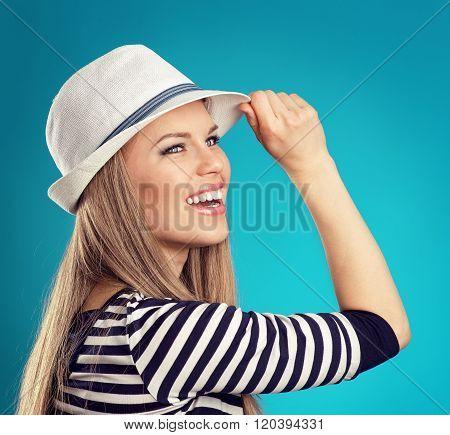 Pretty joyfull girl in hat ready for spring journey over blue