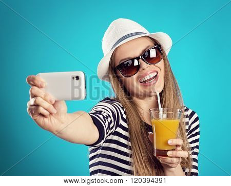 Hot summer girl with coctail taking photo of herself