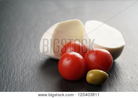 sliced mozarella ball with tomato and olives on slate background