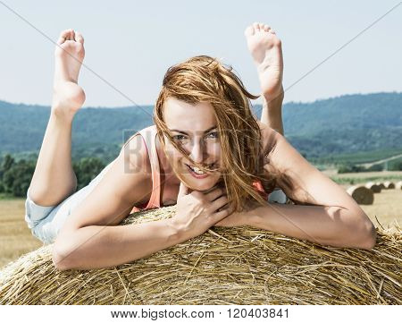 Young Smiling Woman Posing With The Stack Of Straw And Enjoying The Sunshine