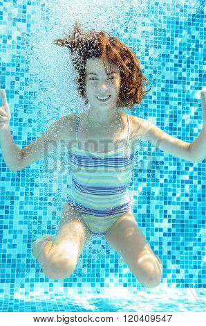 Girl jumps, dives and swims in pool underwater, happy active child has fun in water, kid sport