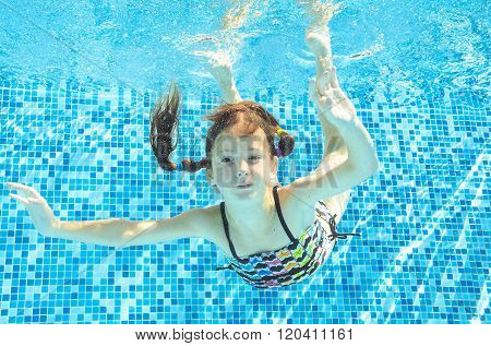 Girl jumps, dives and swims in pool underwater, happy active child has fun under water, kid sport