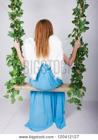 Beautiful young leggy redhaired woman in a long blue dress on a swing, wooden swing suspended from a