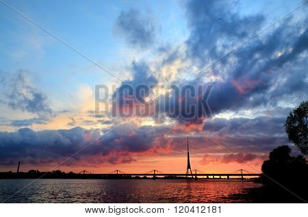 Riga view with Daugava River at a colourful pink sunset. View on Riga bridges and television tower.