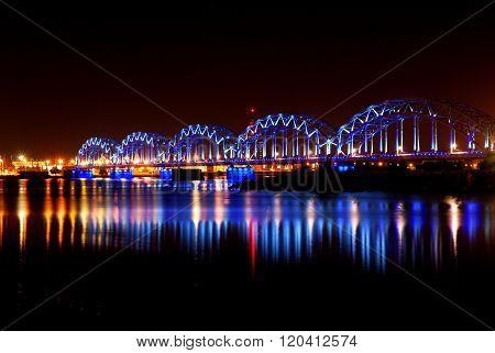 Night panorama of Riga with railway bridge. Colourful illumination reflecting in still Daugava river
