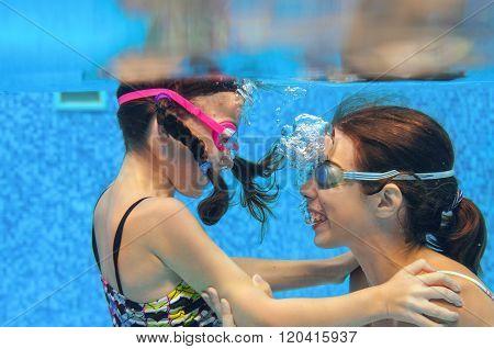 Children swim in pool underwater, happy active girls in goggles have fun under water, kids sport