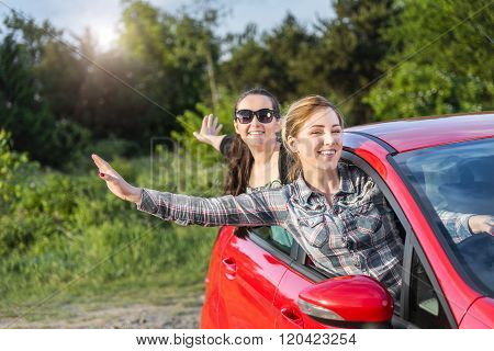 Girls in a red car at sunset. Travel concept.