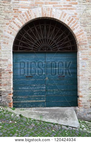 Blue Wooden Door With Arch In Old Brick Wall