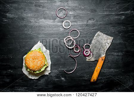 Burger With Onion Rings And An Old Hatchet.  Top View.