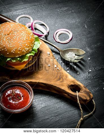 Cooked Hamburger With Ketchup And Onion Rings