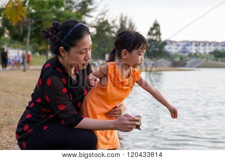 Asian Mother And Daughter Feeding Fish