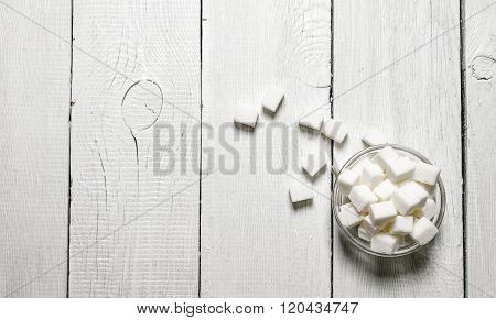 Refined Sugar In The Cup. On White Wooden Background.