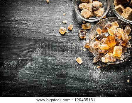 Brown Cane Sugar. On Black Rustic Background.