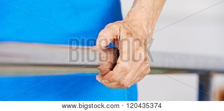 Wrinkled hand of senior woman on handle of a treadmill in physiotherapy