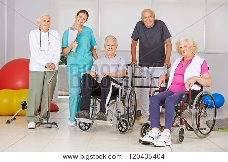 Group of happy senior people at physiotherapy in a nursing home with geriatric nurse
