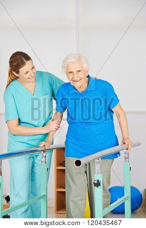 Old woman at movement exercise on horizontal bar in physiotherapy