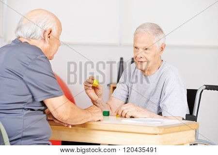Two demented senior men in nursing home talking to each other and playing with building bricks