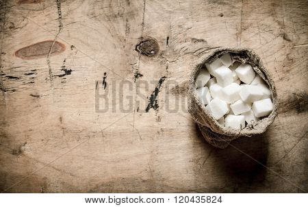 White Refined Sugar In The Bag. On Wooden Background.