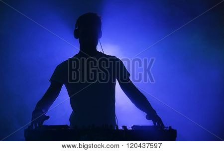 DJ playing music at mixer on color foggy background