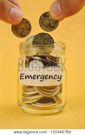 Hand Putting Coin In Jar With Word