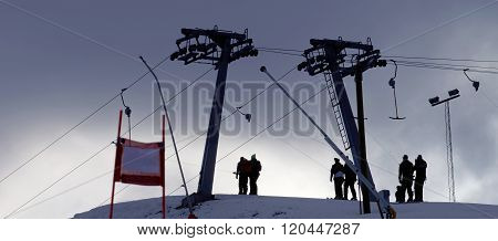 Silhouette Of A Ski Lift And And Skiers In Evening Light