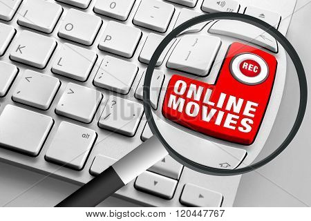 Computer keyboard with red online movies button and magnifying glass