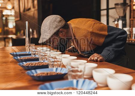 African man at a coffee tasting taking the aroma