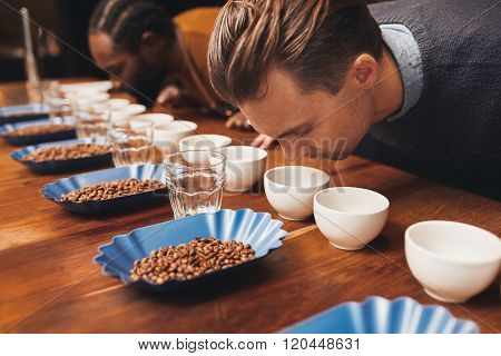Rows of cups and beans with baristas smelling various aromas