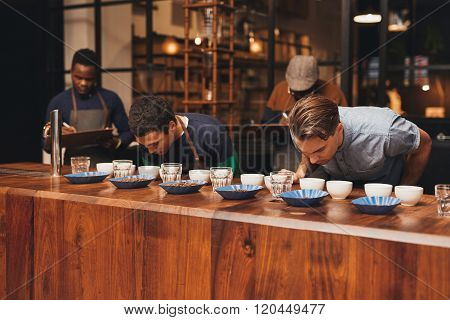 Barista training in a modern roastery with managers taking notes