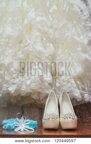 Wedding shoes and blue garter on the dress background