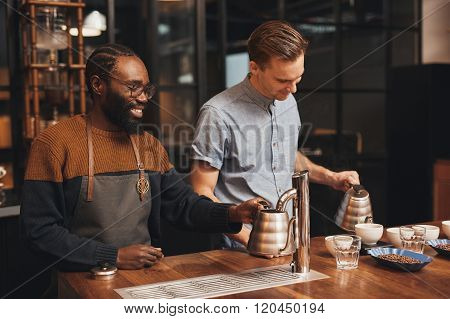 African roastery manager training a barista at wooden counter