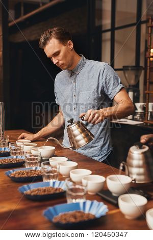 Barista preparing for a coffee tasting with rows of cups