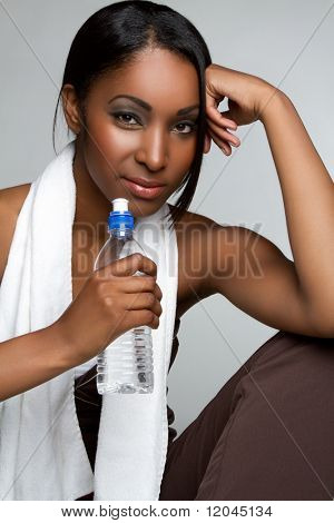 Healthy black woman drinking water