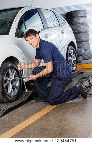 Smiling Mechanic Repairing Car Tire